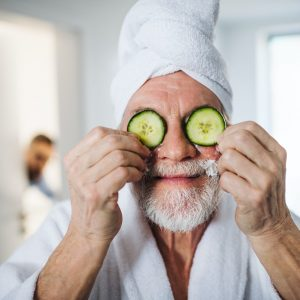 Senior man with cucumber on front of his eyes in bathroom indoors at home
