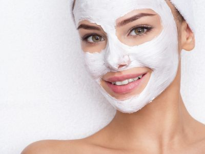 smiling woman in spa salon with cosmetic mask on face